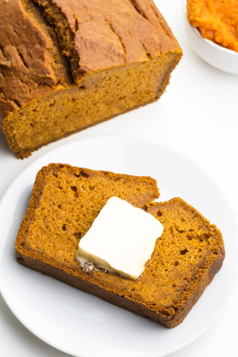 Looking down on a slice of pumpkin bread on a plate. There's a pat of butter on the slice. The rest of the loaf sits nearby alongside a bowl of Pumpkin Puree.