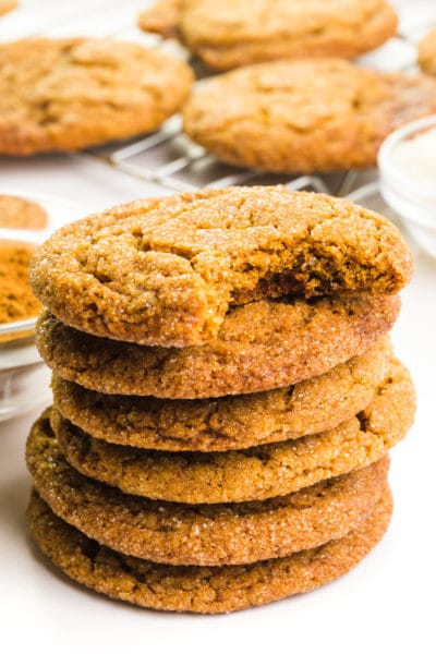 A stack of soft molasses cookie shows the top one with a bite taken out. There are more cookies behind the stack.