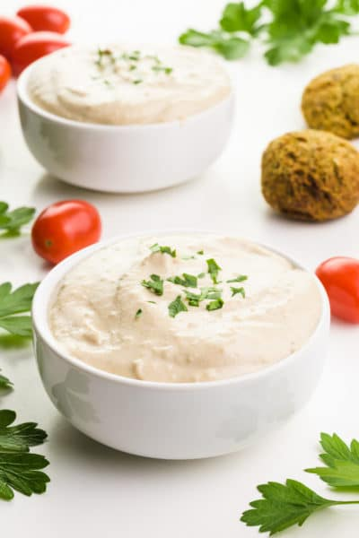 Two bowls of tahini sauce have fresh herbs around them along with red cherry tomatoes and falafel.