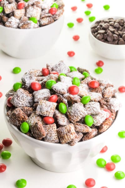 A bowl of Christmas puppy chow has red and green candies around it. There's a bowl of chocolate chips the background and another bowl of the sweet cereal.