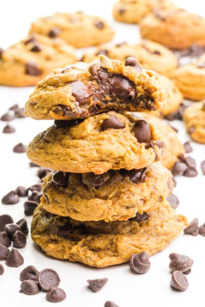 A stack of molasses cookies shows the top one with a bite taken out. There are chocolate chips and more cookies behind the stack.