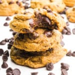 A stack of cookies shows the top one with a bite taken out. There are chocolate chips around it and more cookies in the background.
