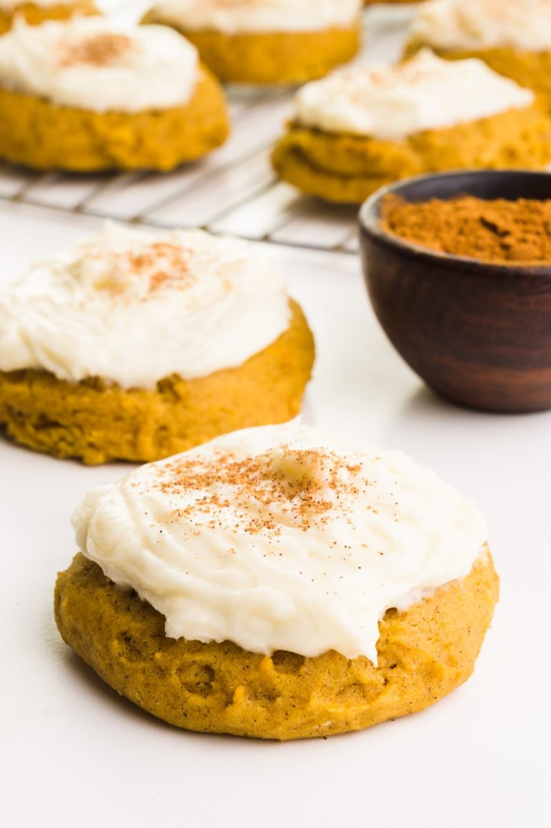 Frosted vegan pumpkin cookies sit on a white counter next to a bowl of spices. In the background is a wire rack with more cookies.