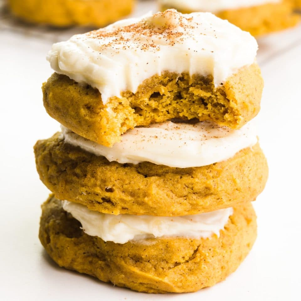 A stack of three vegan pumpkin cookies shows the top one with a bite taken out. There are more cookies in the background.