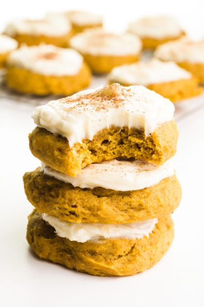A stack of three vegan pumpkin cookies and the top one has a bite taken out. There are more cookies in the background.