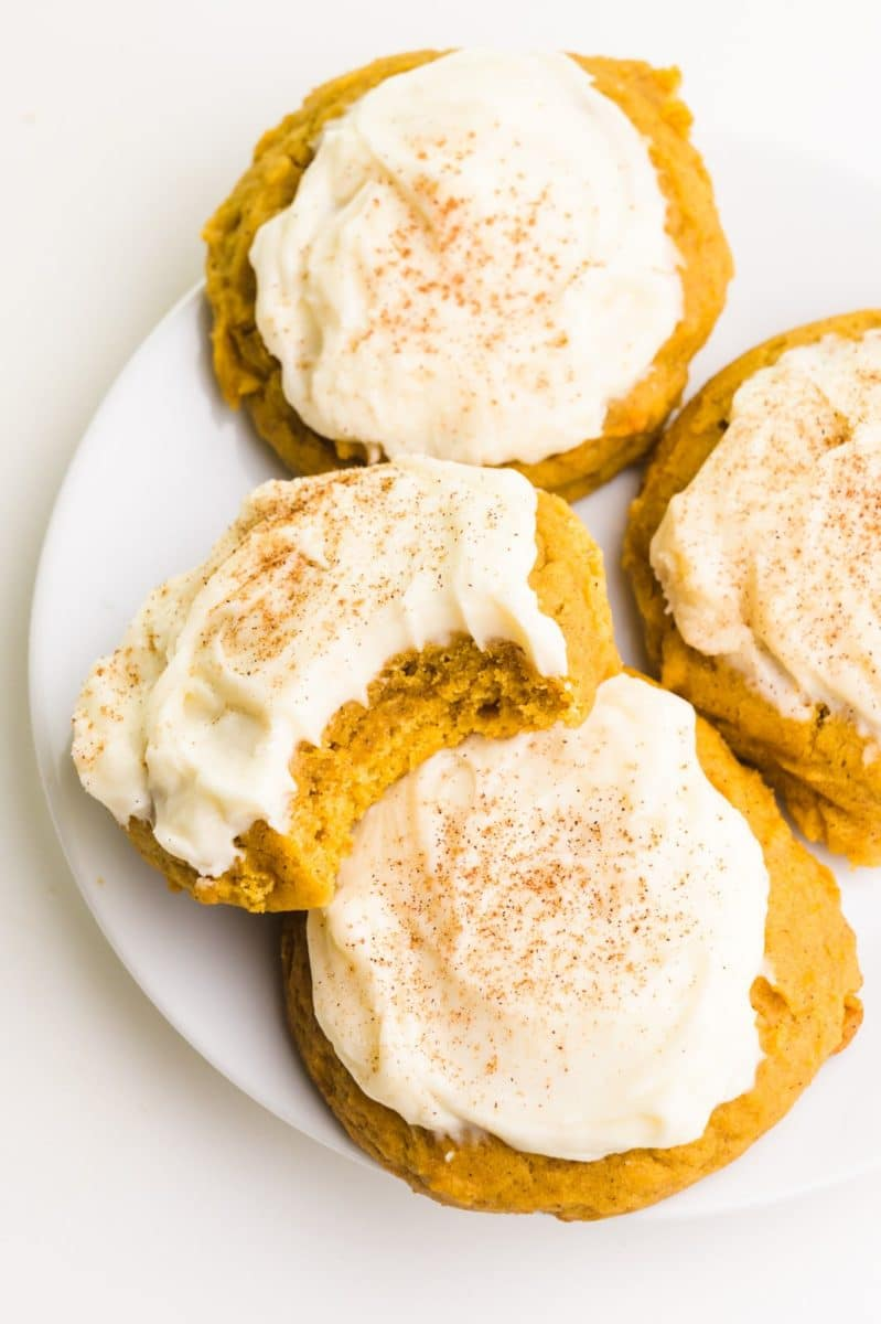 Several frosted pumpkin cookies are on a plate. One has a bite taken out.