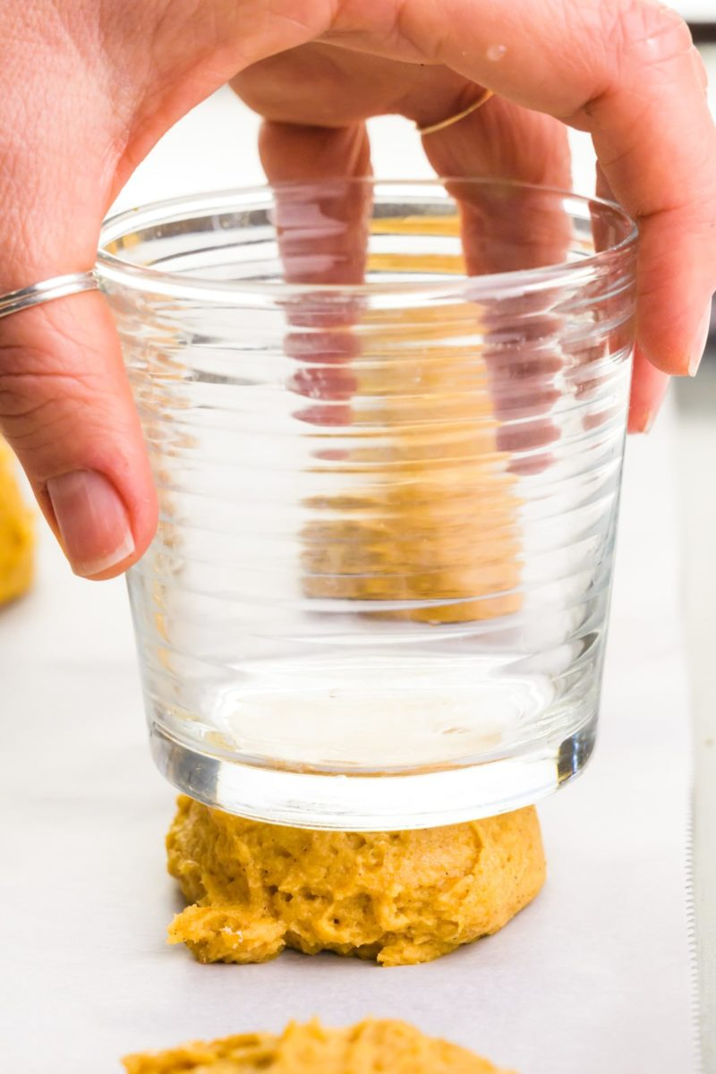 A hand holds a glass and is pressing it down on cookie dough.