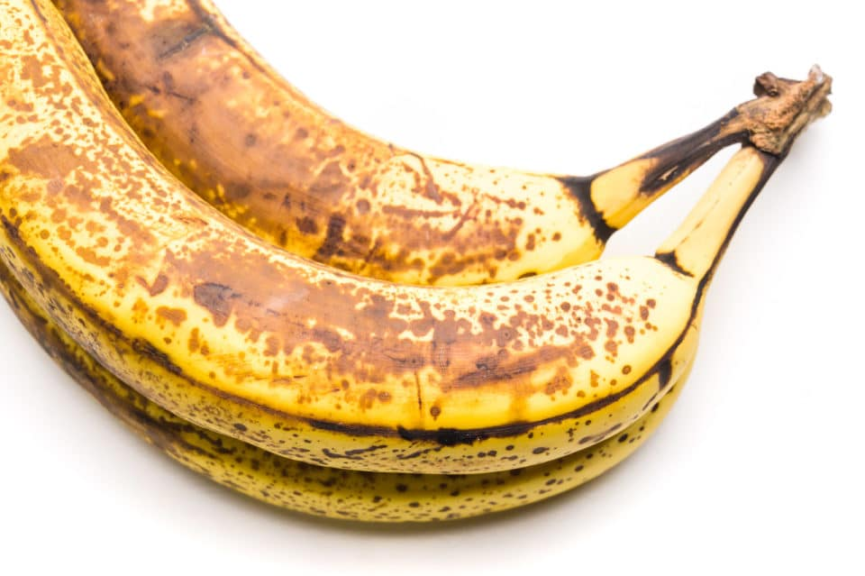 A bunch of 3 very ripe bananas sit on a white counter.