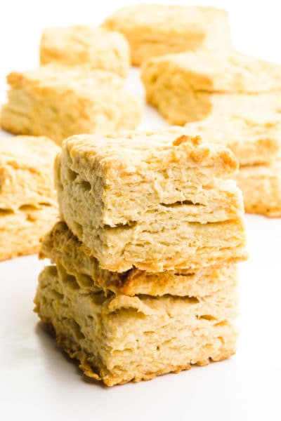 A stack of rectangle vegan biscuits sits in front of other biscuits in the background.