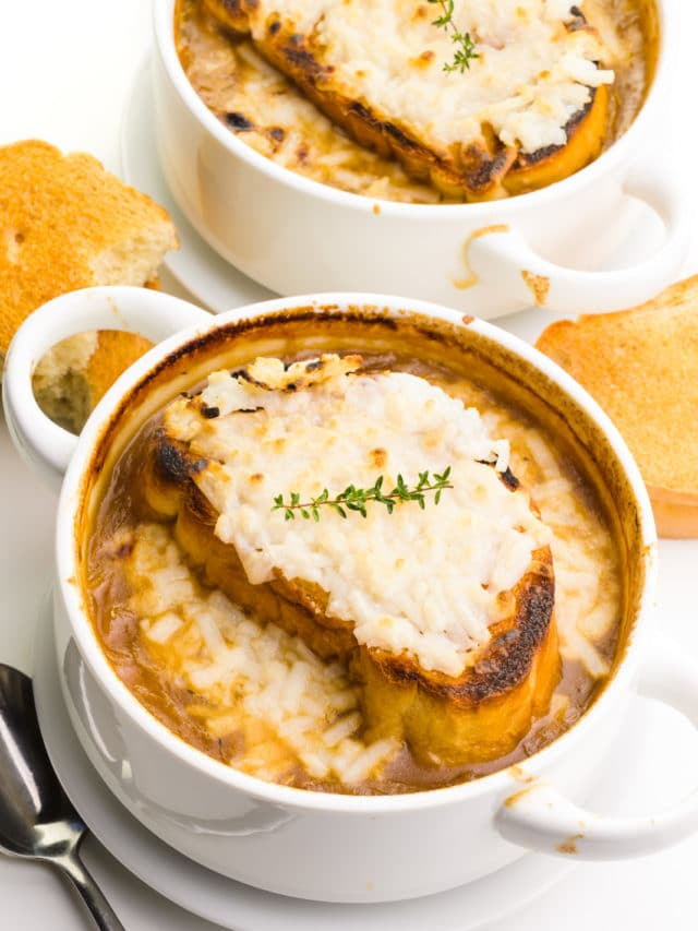 Two bowls of onion soup has melted cheese on top. There are slices of toasted baguette around them and a spoon by the front bowl.