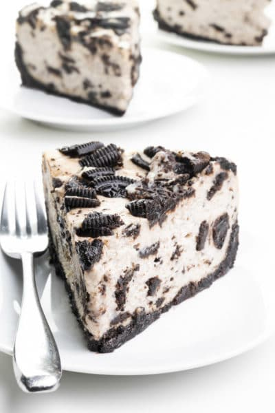 A slice of Oreo cheesecake sits on a plate with a fork beside it. There are two more slices on plates behind it.