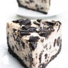 A slice of vegan Oreo cheesecake sits on a plate. Another slice is behind it.