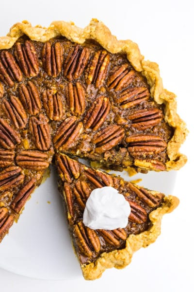 Looking down on a vegan pecan pie with a slice cut out. The slice has whipped cream on top.