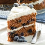 A slice of 2-layer vegan blueberry cake with fresh blueberries on top sits in front of the whole cake.