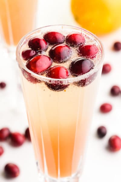 A close-up image of a glass of holiday punch shows fresh cranberries and sparkling water fizzes at the tope. There are fresh cranberries, an orange, and another glass in the background.