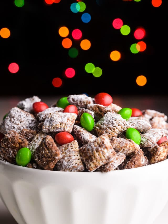 A bowl of chocolate Christmas muddy buddies has a dark background and holiday lights behind it.