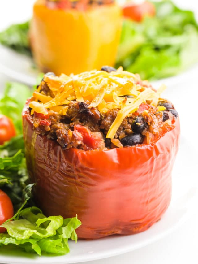 A vegan stuffed pepper sits on a white plate with a salad beside it. Another one is on a plate behind it.