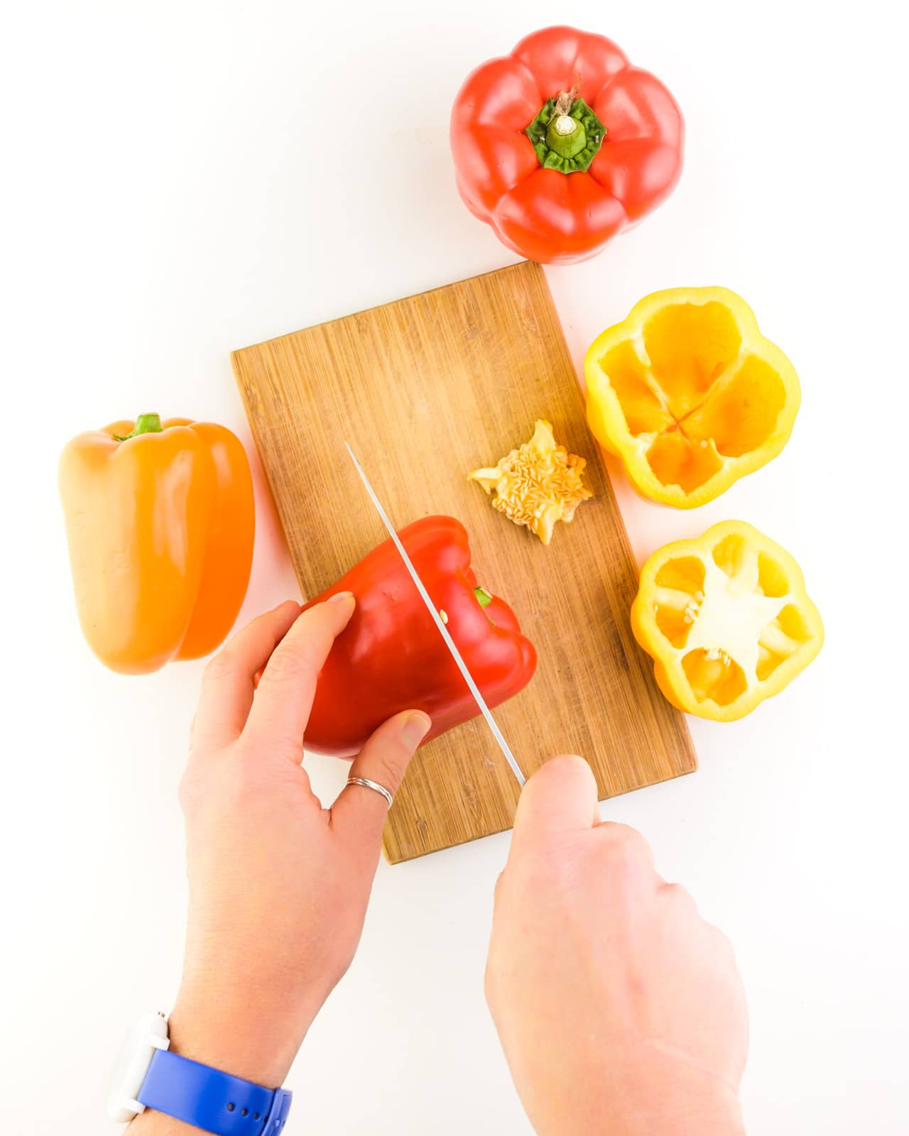 Colorful bell peppers sit on and near a cutting board. A hand holds one pepper while the other hand holds a knife, cutting the top off of it.