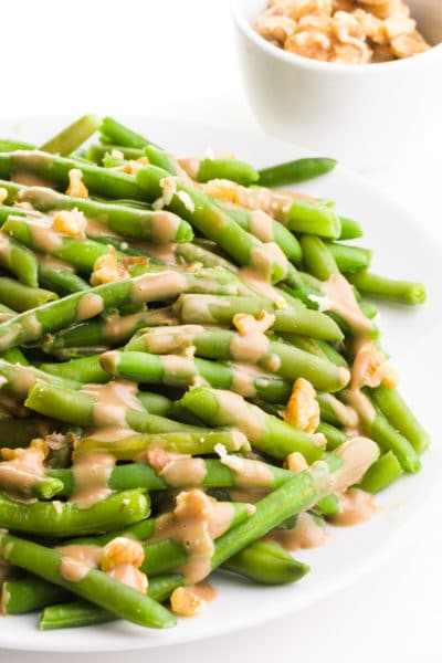 Balsamic green beans have chopped walnuts and glaze over the top. There's a bowl with walnuts in the background.