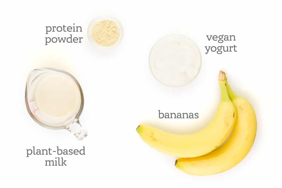 """Ingredients are on a white counter. The labels read, """"bananas, plant-based milk, protein powder, and vegan yogurt."""""""