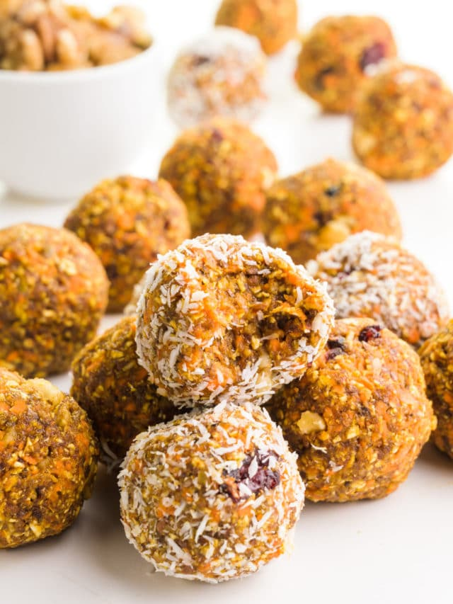 A group of carrot cake energy bites sits around a bowl of walnuts. One of the treats has a bite taken out of it.