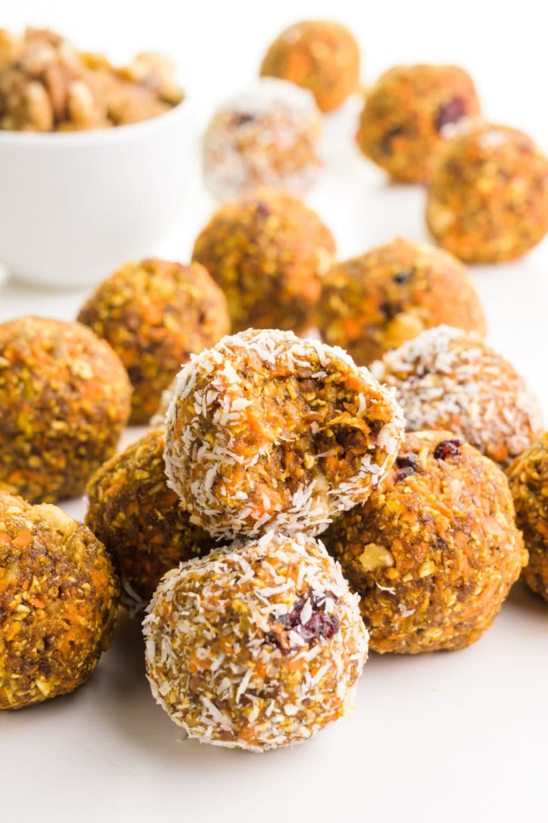A group of carrot cake energy balls sits around a bowl of walnuts. One of the treats has a bite taken out of it.