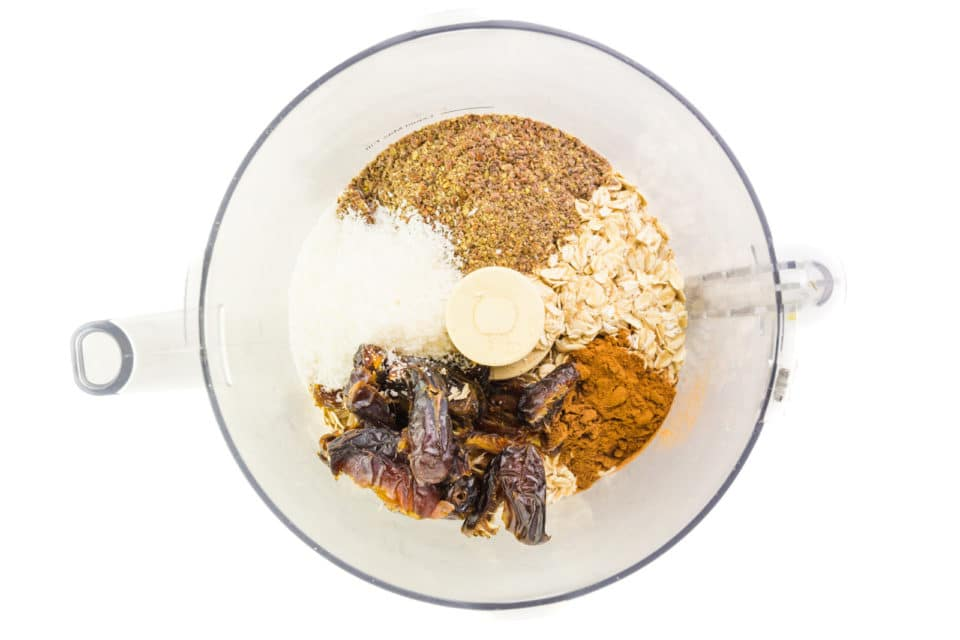 Looking down on a food processor bowl full of oats, ground flax, coconut flakes, dates, and spices.