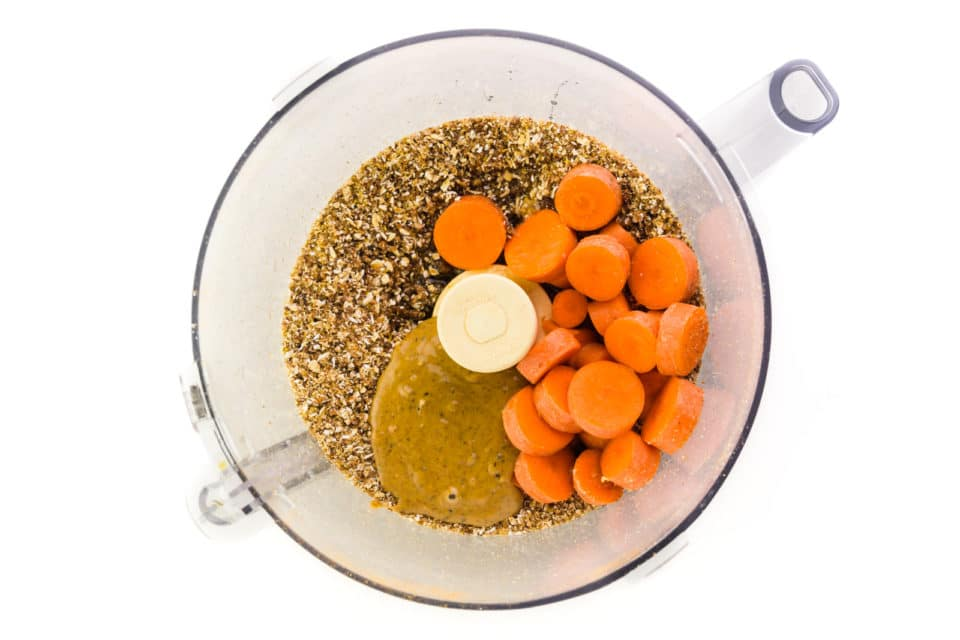 A food processor bowl has ground ingredients in it along with nut butter and carrot slices.