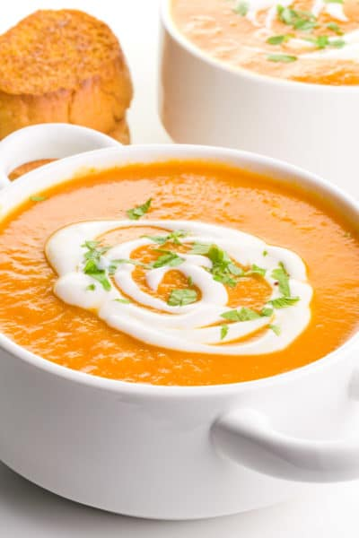 A bowl of carrot ginger soup has cream drizzled over the top and chopped parsley. There's a another bowl of soup behind it along with a stack of toasted bread.