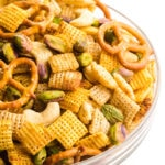 A large bowl is full of gluten-free Chex mix, featuring pretzels, nuts, and more.