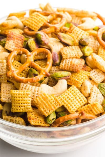 A large bowl holds Chex mix, with corn Chex, rice Chex, gluten-free pretzels, and nuts.