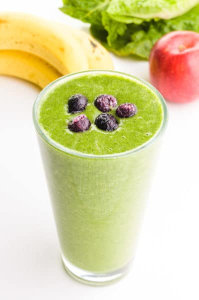 A green smoothie has blueberries on top. There are bananas, apples, and greens behind it.