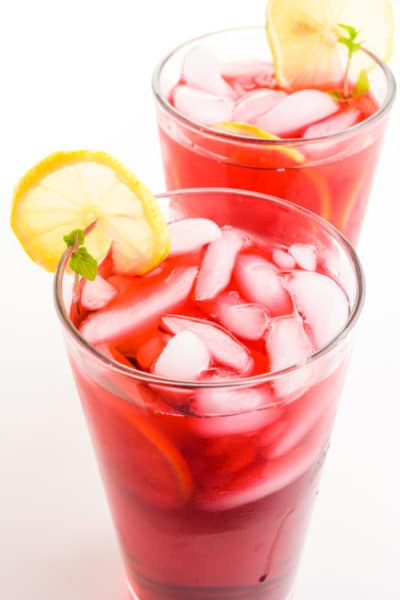Two glasses of hibiscus tea have lemon slices on the side and ice in the glasses.