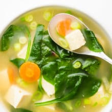 Looking down on a bowl of soup with a spoon in it. There are ingredients like greens, carrots, tofu, and green onions on top.