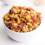 A bowl of peanut butter granola has dried cranberries, pumpkin seeds, nuts, and more.