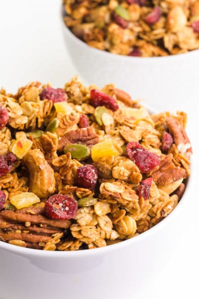 A bowl of peanut butter granola features dried cranberries, nuts, and more. There's another bowl with granola behind it.