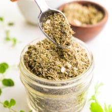 A spoon holds seasoning over a bowl of more seasoning. There are fresh herbs and bowls with more seasoning behind it.