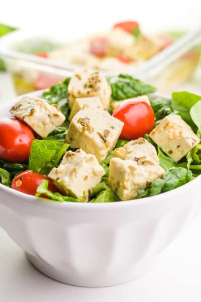 A bowl holds a salad full of greens, cherry tomatoes, and tofu feta cubes.