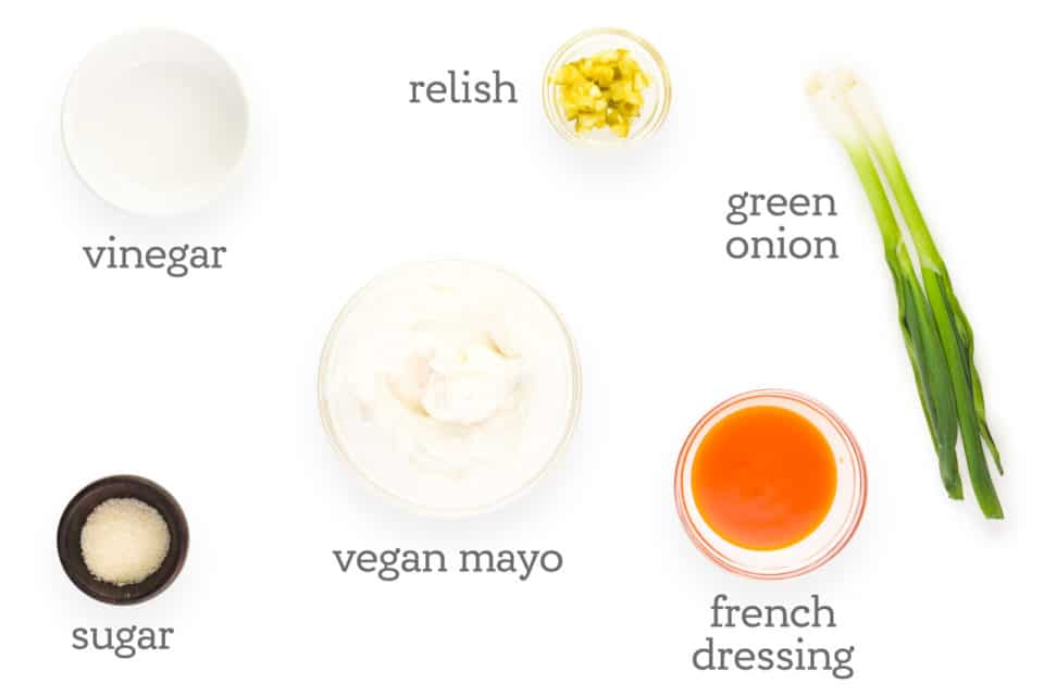 """Ingredients are laid out on a table. The labels read, """"vinegar, relish, green onions, French dressing, vegan mayo, sugar."""""""