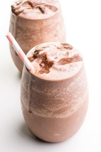 Two glasses hold vegan chocolate milkshakes with chocolate syrup and paper straws.