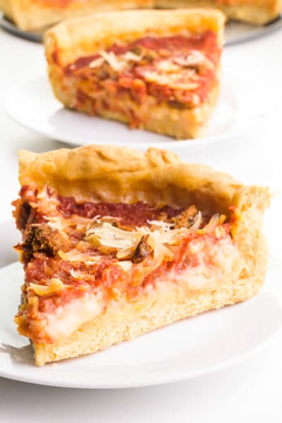 A slice of vegan deep-dish pizza sit on a plate. Another slice is on a plate behind it with the rest of the pizza.