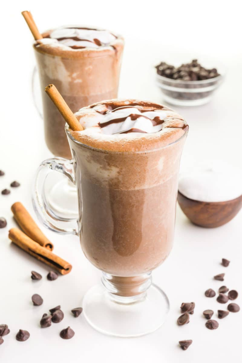 Two glass mugs hold vegan hot chocolate both with cream on top and cinnamon sticks. There are chocolate chips and cinnamon sticks around the mugs and a bowl of whipped cream and chocolate chips.