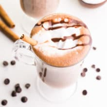 Looking down on a mug full of hot cocoa with whipped cream and chocolate syrup on top. There's a cinnamon stick in the mug and more beside. There are chocolate chips around the mug.