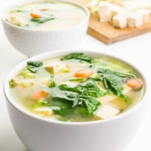 A bowl of vegan miso soup shows pieces of tofu, greens, carrots and more on top. A cutting board in the background has more ingredients, like tofu and green onions.