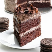 A slice of vegan Oreo cake has stacks of Oreo cookies around it and the rest of the cake behind it.