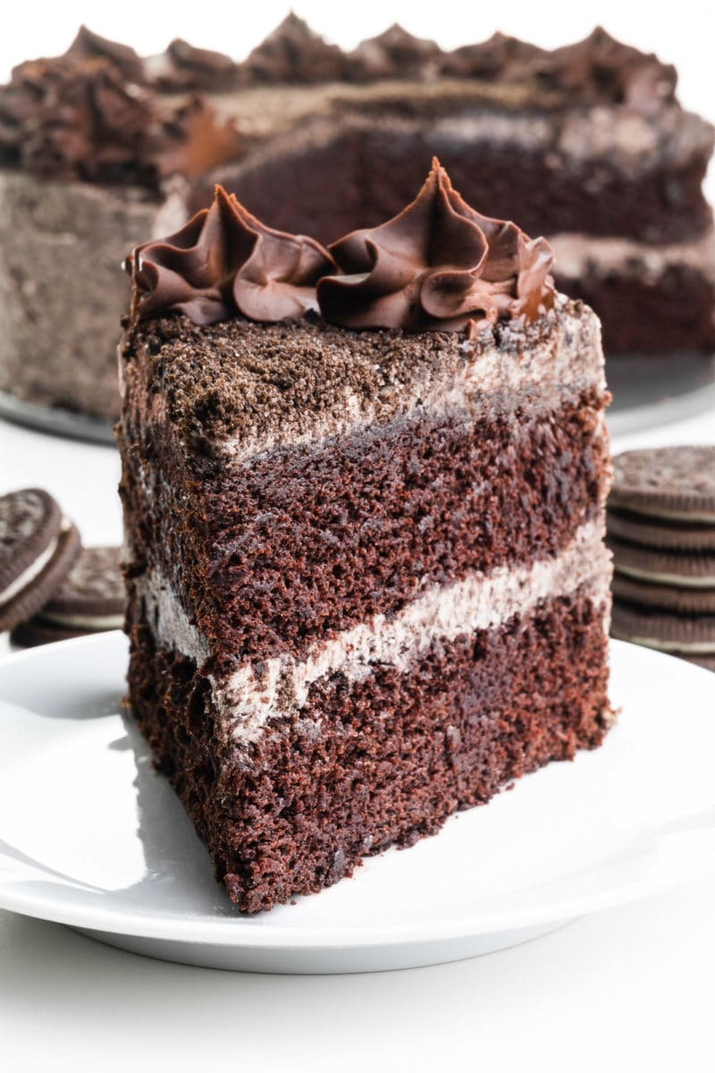 A slice of layered Oreo cake  sits in front of the rest of the cake. There are stacks of Oreo cookies behind it.