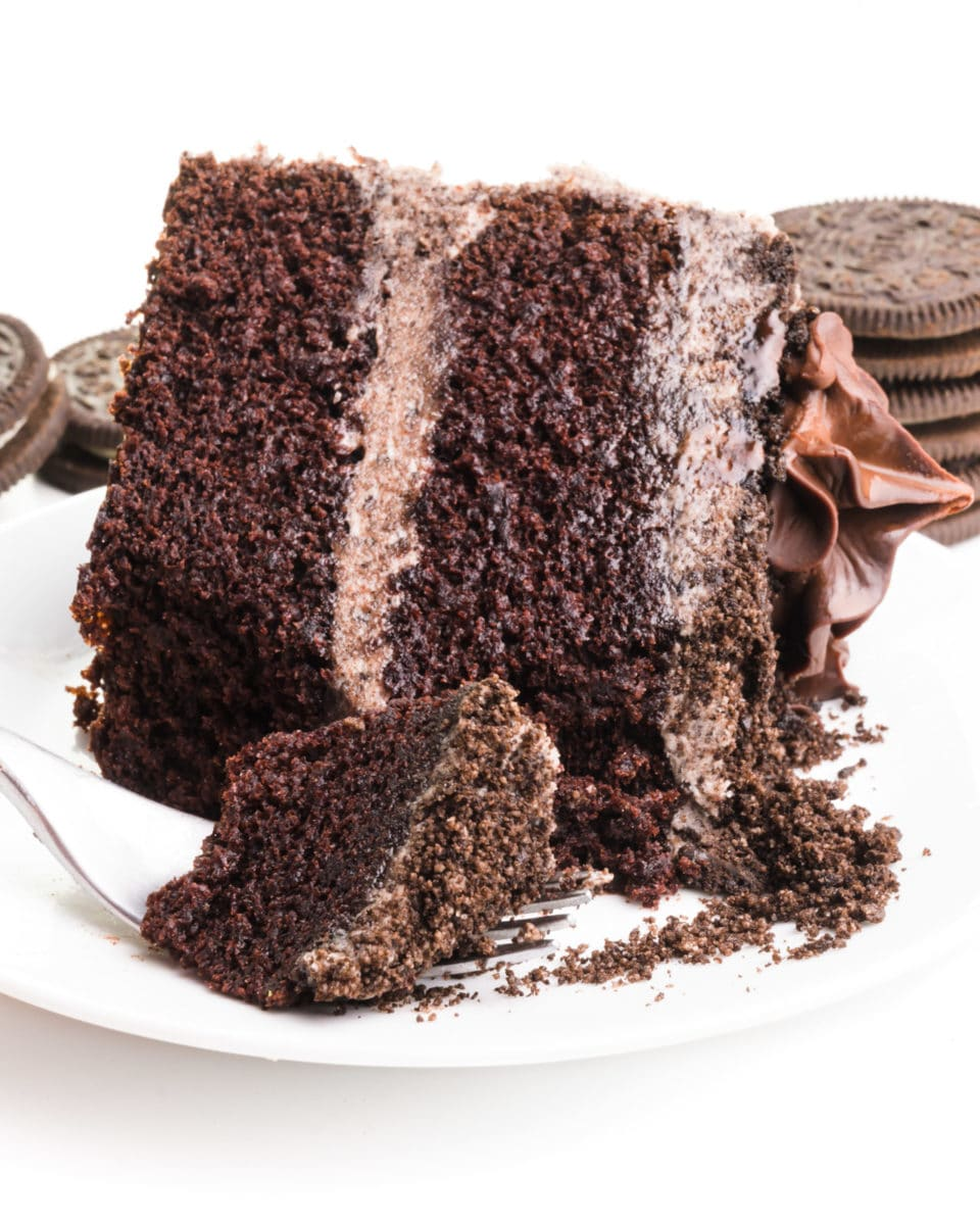 A slice of Oreo cake is on its side and a piece of it is on a fork, showing the frosting. There are cookies stacked in the background.