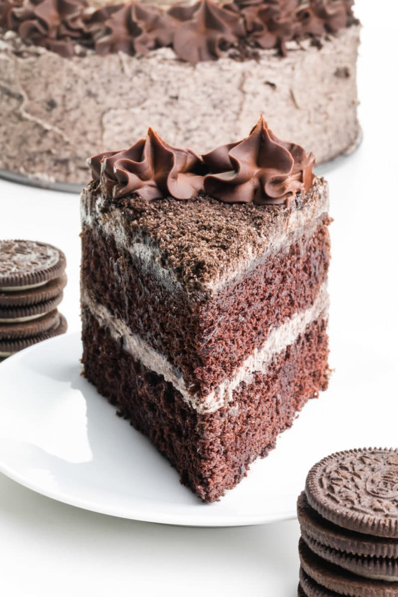 A slice of chocolate cake sits on a plate with chocolate sandwich cookies stacked in front and behind it. The rest of the cake is behind it too.