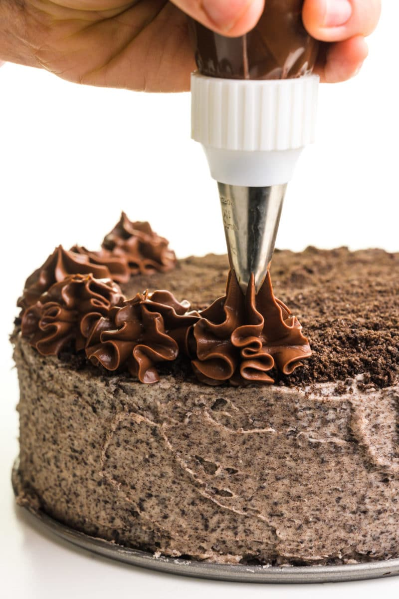A hand holds a piping bag, adding chocolate ganache stars on top.