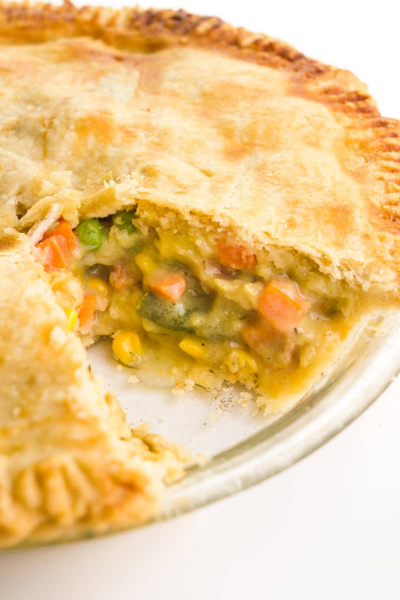 A savory pot pie has a slice cut out revealing vegetables and vegan chicken inside.
